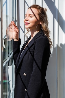 Блондинка в черном костюме стоит у окна и наслаждается солнечным светом.