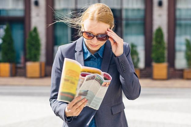 Блондинка в сером пиджаке и коричневых очках с удивлением читает свежую прессу