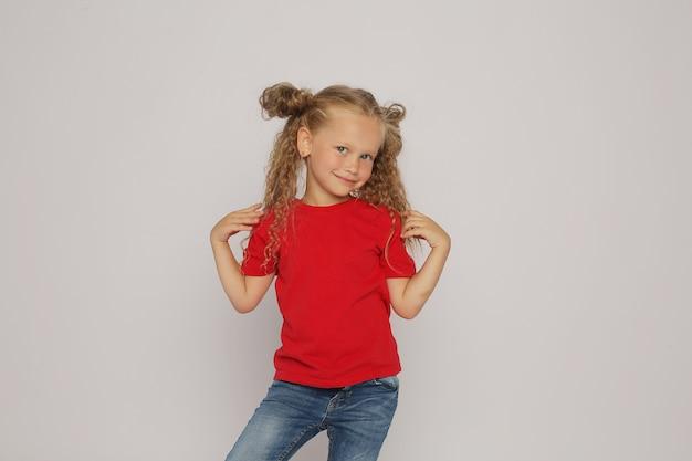 Блондинка в красной майке и джинсах с хвостиками демонстрирует эмоции