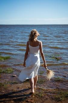 흰 드레스에 금발 소녀가 꽃의 꽃다발을 들고 바다로 맨발로 걷는다.
