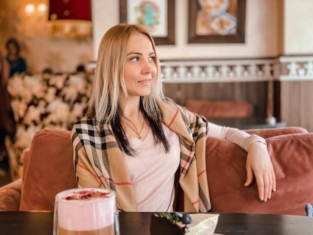 Блондинка с шарфом на плечах в нежно-розовом свитере сидит в уютном ресторане, расслабившись, выпивает кофе и кусок торта у нее на столе.