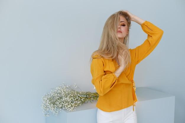 ファッショナブルな背景にマスタードシャツを着た金髪が彼女の健康な髪に触れます。美的