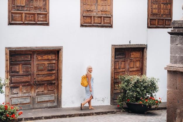 배낭을 메고 선드레스를 입은 금발의 한 여성이 카나리아 제도 테네리페 섬에 있는 가라치코 구시가지의 거리를 걷고 있습니다.