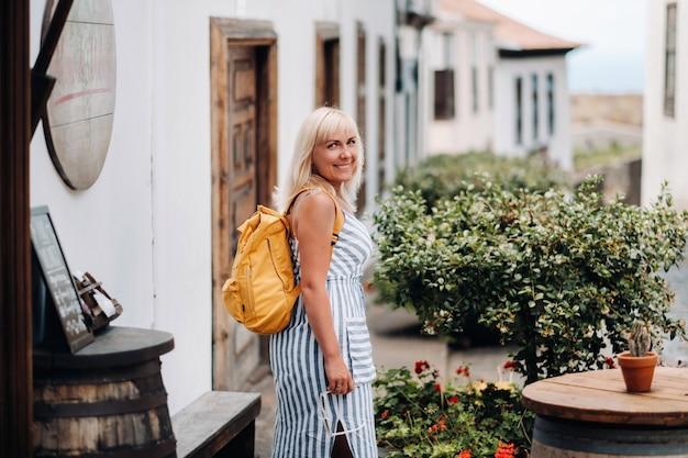 배낭이 달린 sundress에 금발이 테 네리 페 섬에있는 garachico의 구시 가지 거리를 따라 걷고 있습니다. 스페인, 카나리아 제도.