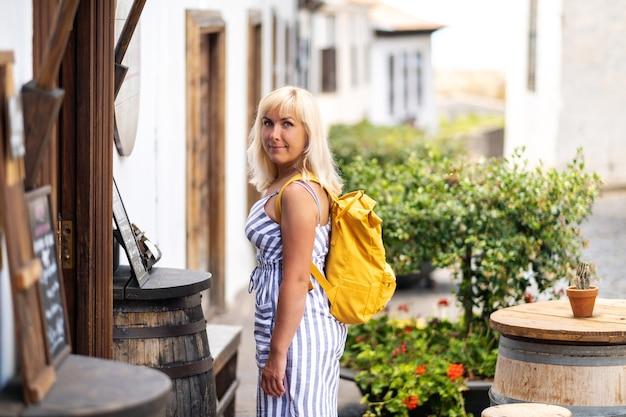 テネリフェ島のガラチコの旧市街の通りをバックパックを背負ったサンドレスを着た金髪が歩きます。スペイン、カナリア諸島。