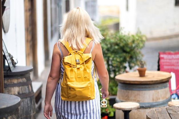 배낭이 달린 sundress에 금발이 테 네리 페 섬의 garachico 구시 가지 거리를 따라 걷고 있습니다.