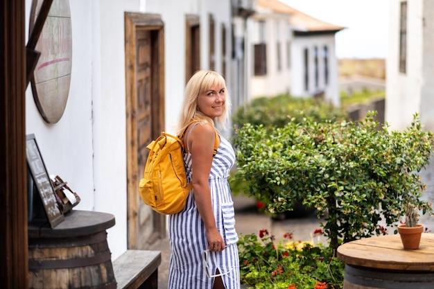 배낭이 달린 sundress에 금발이 테 네리 페 섬에있는 garachico의 구시 가지 거리를 따라 걷는다.