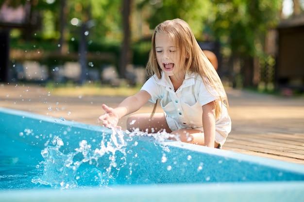 Блондинка маленькая девочка сидит возле бассейна