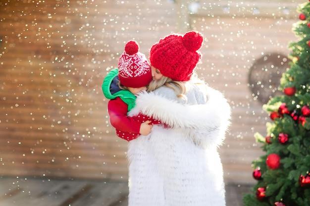Светловолосая мать держит смеющегося сына в рождественском свитере и красной шляпе под снегом на фоне елки. фото высокого качества