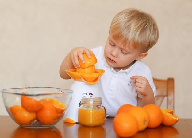 금발의 예쁜 아이가 신선한 오렌지 주스를 만들고있다