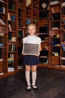 Блондинка-школьница в школьной форме держит пустой дощатый лист в библиотеке