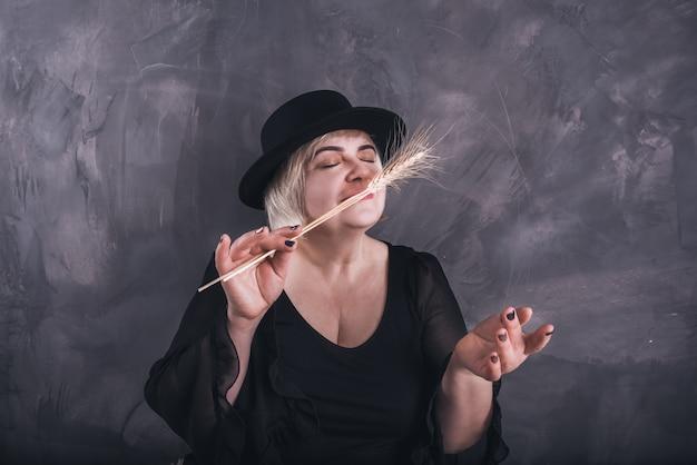 黒い服と黒い帽子をかぶった金髪の短い髪のぽっちゃりした年上の女性。ヨーロッパの女性が黄色い乾燥小麦を手に持ってその香りを吸い込む