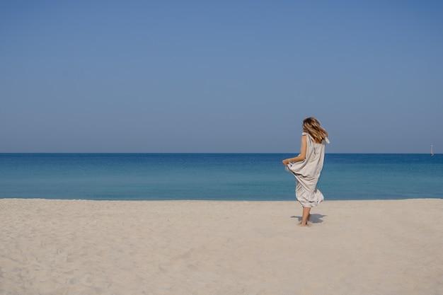 青い空と海を背景に砂浜でジャンプして踊る羽ばたき髪のマキシリネンドレスを着た金髪の笑顔の女の子