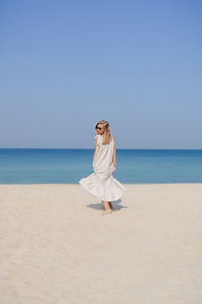 펄럭이는 머리 점프와 모래 해변에서 춤을 함께 맥시 린넨 드레스에 금발 웃는 소녀