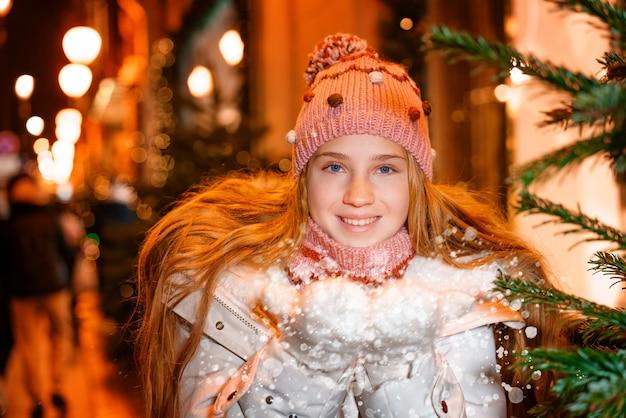 긴 머리에 모자를 쓰고 겨울 옷을 입은 금발의 십대는 축제의 겨울 저녁에 ...