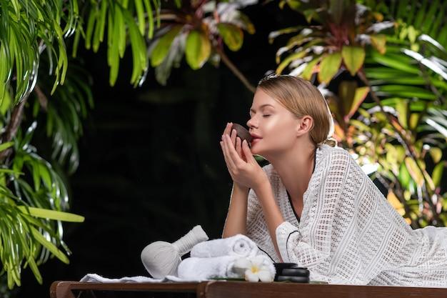 Блондинка с цветком в волосах и белом пальто касается горячих камней для массажа