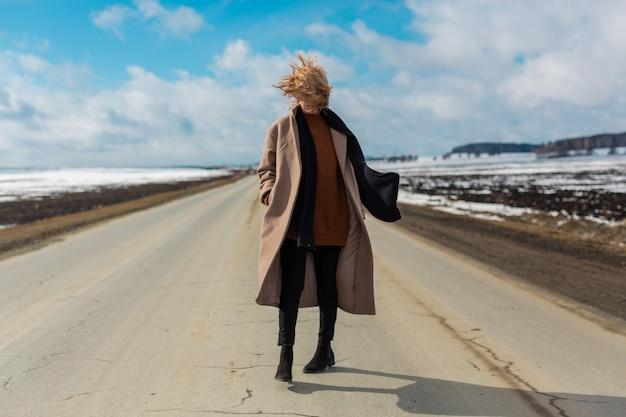 검은 색 스카프를 낀 베이지 색 코트를 입은 금발의 여인이 푸른 하늘과 눈 덮인 들판을 배경으로 텅 빈 고속도로를 유쾌하게 걸어 간다.