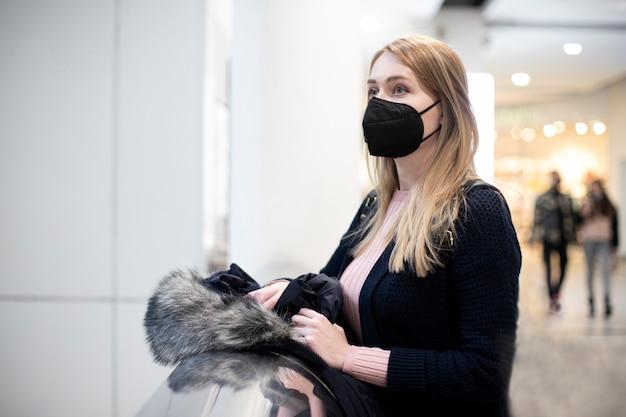 友人を待っているウイルスからの黒い医療マスクのブロンドの女性