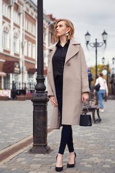 コートを着て財布を運ぶ金髪の女性が秋の街を歩いている