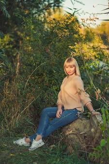 짧은 머리를 한 니트 스웨터를 입은 금발의 여성이 숲 속의 연못 배경에 있는 쓰러진 나무에 앉아 있습니다. 가을 숲에서 야외 레크리에이션