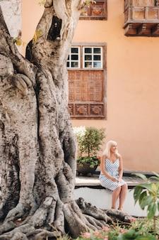 선드레스를 입은 금발의 여성이 카나리아 제도 테네리페 섬에 있는 가라치코 구시가지의 거리에 앉아 있습니다.