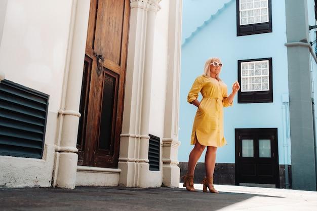 テネリフェ島のララグーナの旧市街の通りに黄色いサマードレスを着た金髪の女性が立っています。スペイン、カナリア諸島。