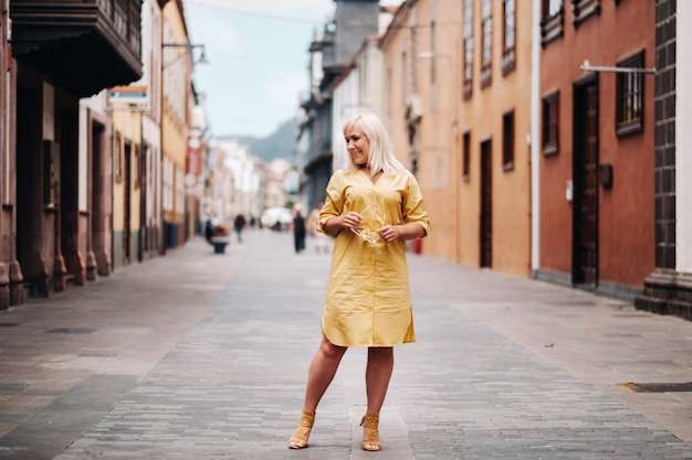 Блондинка в желтом летнем платье стоит на улице старого города ла-лагуна на острове тенерифе, испания, канарские острова.