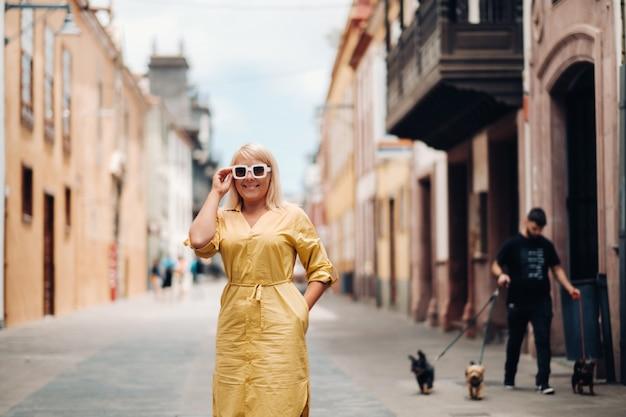 노란색 여름 드레스를 입은 금발의 여성이 카나리아 제도 테네리페 섬의 라 라구나 구시가지 거리에 서 있습니다.