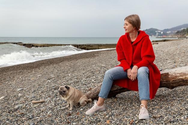赤いコートを着た金髪の女性が海岸に座っています。晴れた晴れた日にビーチでパグ。