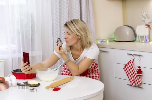 Блондинка на кухне готовит рождественский торт и делает селфи на смартфоне