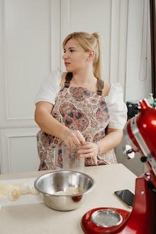 金髪の女性が手でレモンジュースをキッチンのブレンダーカップに押しつぶしています。