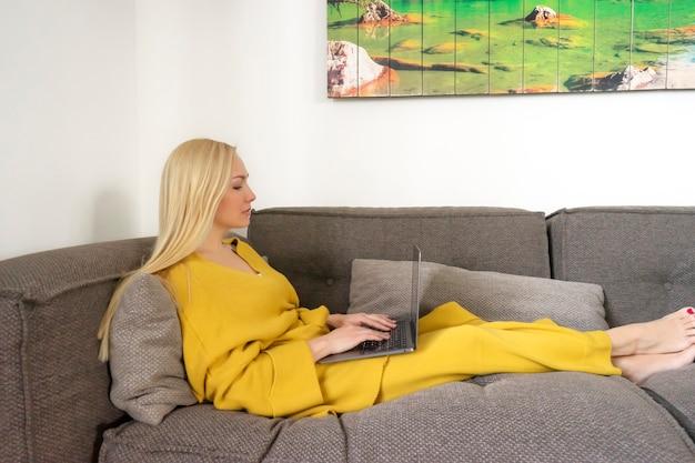 금발의여자가 노트북을 들고 집에서 일하고있다. 트렌디 한 색상. 2021 년 올해의 색상
