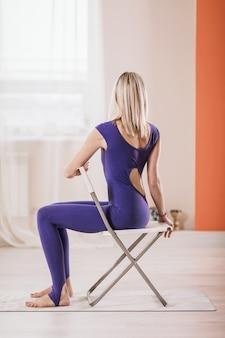 요가 연습 금발의 여자는 창가에 스튜디오에서 의자와 트위스트를 수행