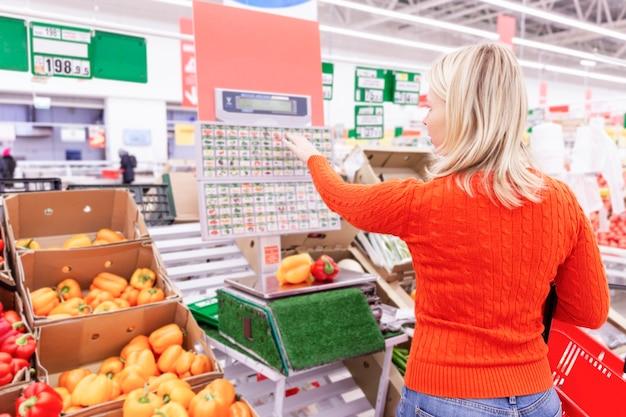Блондинка взвешивает фрукты в супермаркете. вид сзади.