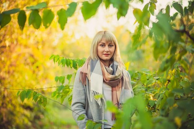 짧은 머리를 한 금발의 여성이 회색 양모 코트와 격자 무늬 스카프를 입고 숲을 걷고 있다