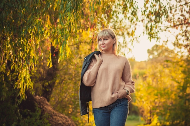 짧은 머리를 한 금발의 여성이 니트 스웨터를 입고 어깨에 가죽 재킷을 메고 숲 속을 걷고 있습니다. 가을 숲에서 야외 하이킹 프리미엄 사진