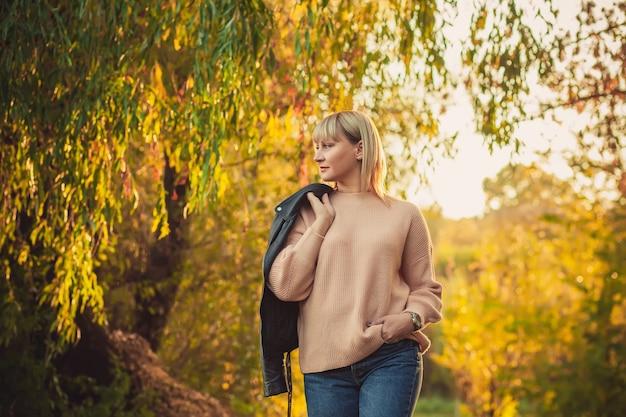 짧은 머리를 한 금발의 여성이 니트 스웨터와 어깨에 가죽 재킷을 입고 숲을 걷고 있다