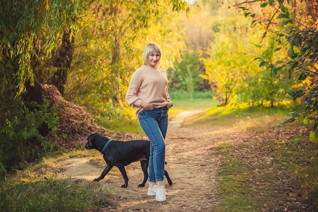 短い髪型の金髪の女性が、ニットのセーターと大きな黒い犬のロットワイラーで森の中を歩きます。秋の森でのアウトドアハイキング