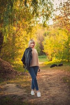 短い髪型の金髪の女性が、ニットのセーターと2匹の大きな黒い犬のロットワイラーで森の中を歩きます。秋の森でのアウトドアハイキング