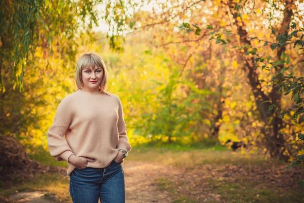 짧은 머리를 한 금발의 여성이 니트 스웨터를 입고 숲을 걷고 있습니다. 가을 숲에서 야외 하이킹
