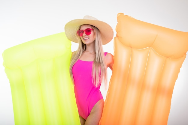 분홍색 수영복과 모자에 금발의 젊은 여자가 두 개의 에어 매트리스를 보유