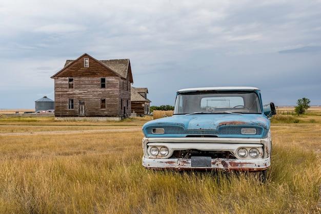 青と白のクラシックなピックアップトラックとゴーストタウンのロブサートskの廃屋