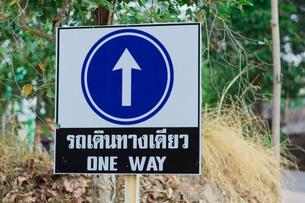 青い矢印のサインとそれはタイ語と英語で片道旅行を示しています