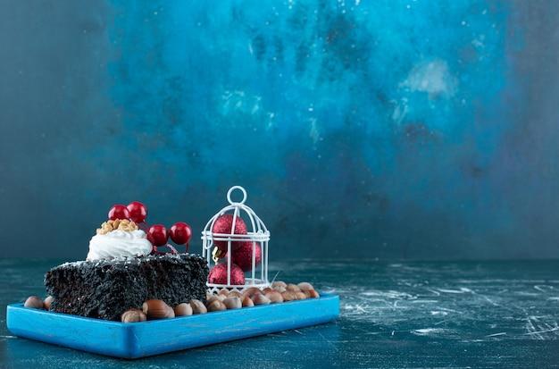 초콜릿 케이크 한 조각과 마카다미아 너트가 있는 블루 보드. 고품질 사진