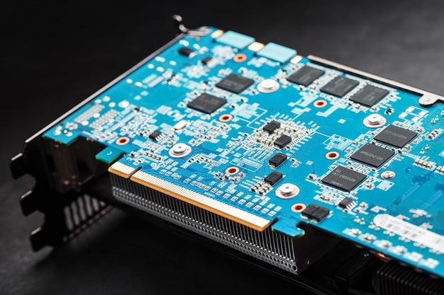Синяя плата с чипами и процессором игровой видеокарты. прогрессивная система охлаждения видеочипа, процессора и памяти. сведения о компьютере