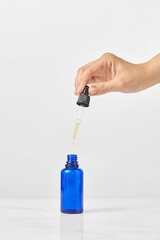 ライトグレーのテーブル、コピースペースに対して女性の手に天然医療大麻エッセンシャルcbdオイルの青いボトルとピペット。医療目的での大麻の使用。