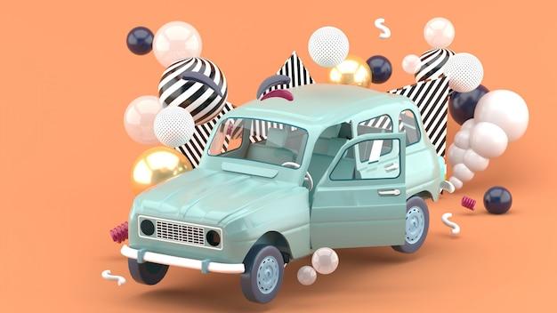 カラフルなボールオンオレンジに囲まれた青い車。 3dレンダー
