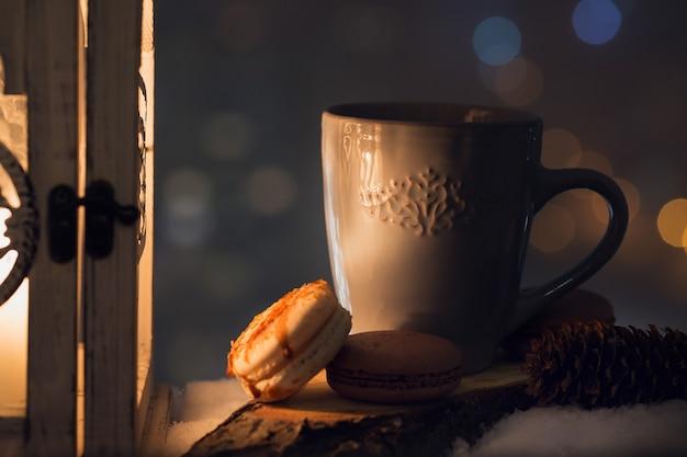 雪の中で温かい飲み物とクッキーが入った青いカップ。冬の休日のコンセプト。