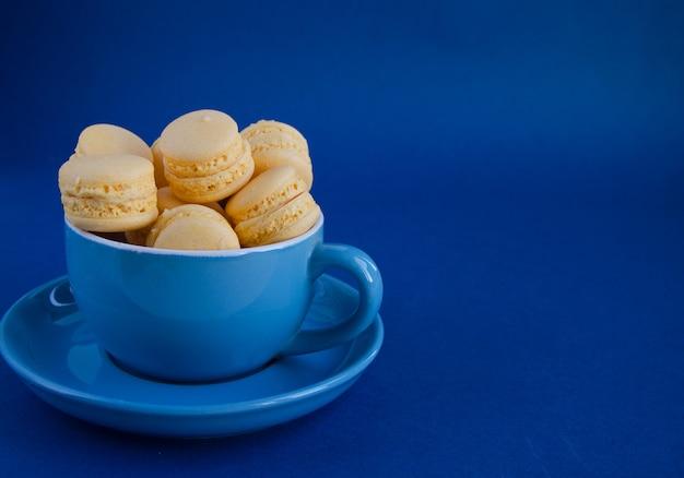 青色の背景にマカロンと青いカップ