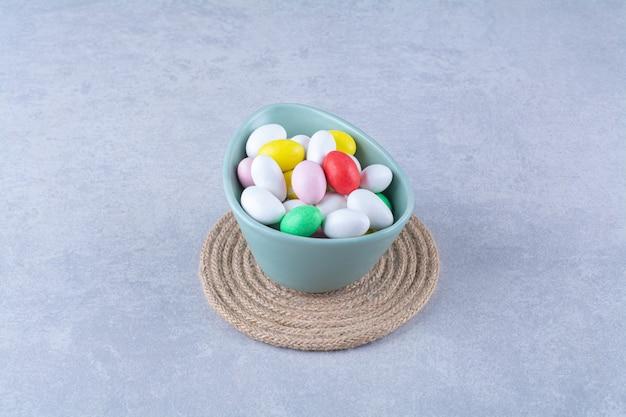 Голубая глубокая миска, полная красочных бобовых конфет на сером фоне. фото высокого качества